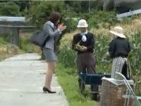 保険屋の女性が畑で仕事中の夫婦を訪ねる