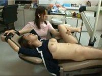 挿入の為に足を開かせる歯科助手
